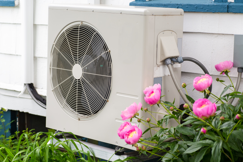 Air Source Heat Pump unit on the side of a home among the flowers.